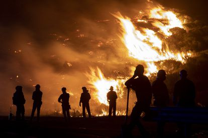 Forest firefighters and local residents observe the blaze last August in Navalacruz, Ávila.