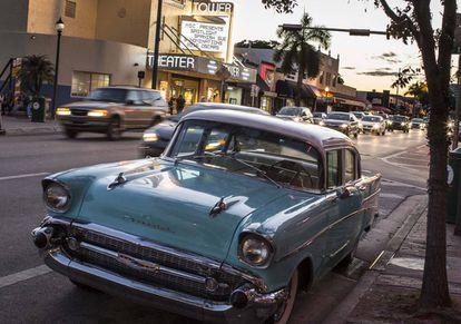A vintage Chevrolet parked in front of the art nouveau Tower Theater movie house.