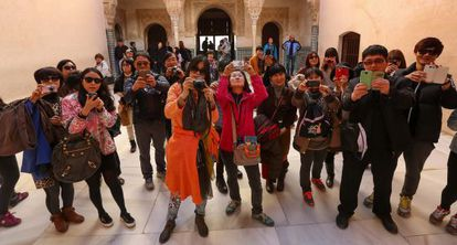 A group of tourists photographs the inside of the Alhambra.