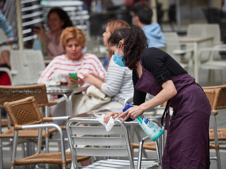 A waiter disinfects a table at a restaurant in Pamplona, Navarre.