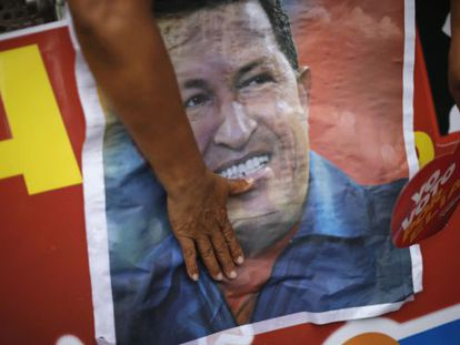 A Chávez supporter touches a campaign poster of the president during a PSUV rally Sunday