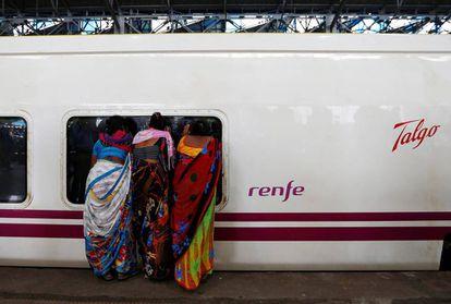 Women peeking inside a Talgo train in Mumbai.
