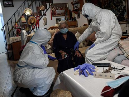 Healthcare workers examine suspected coronavirus patient at her home in Madrid.