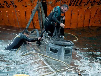 """Spanish Civil Guard divers stand over the """"narco-submarine."""""""