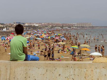 Holidaymakers on the beach at Malvarrosa, Valencia. The region is one of the most popular for tourists.