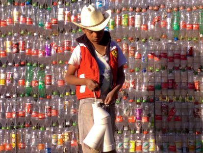 A boy outside a wall made from plastic bottles in Tetela, Mexico.