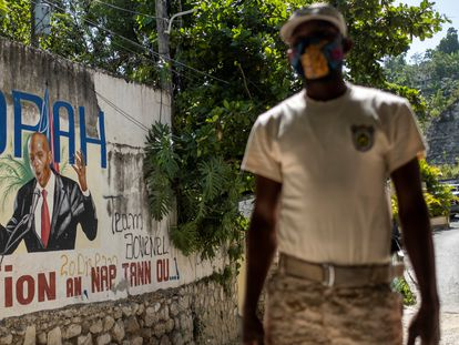 A police officer near a sign depicting Jovenel Möise outside his official residence in Port-au-Prince on Sunday.