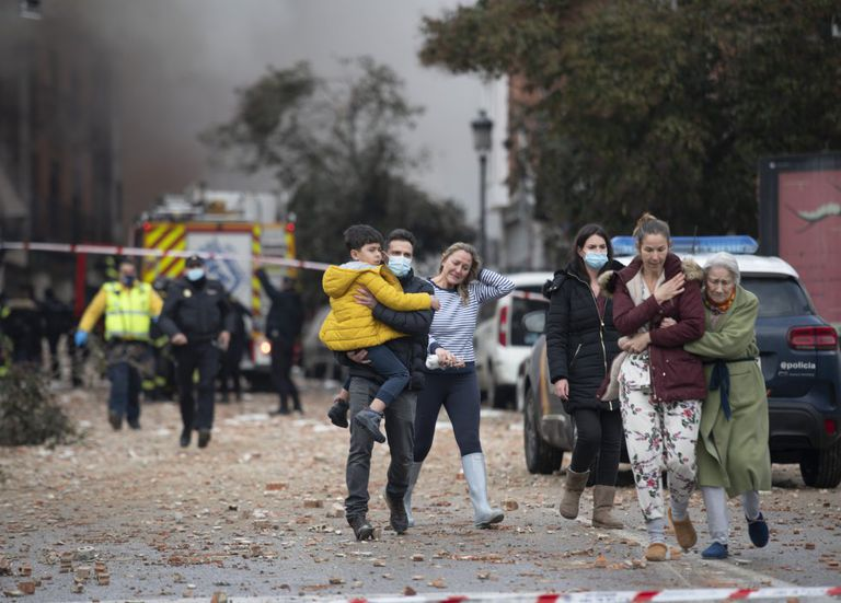 Members of the public leave the site of the explosion in Madrid today.