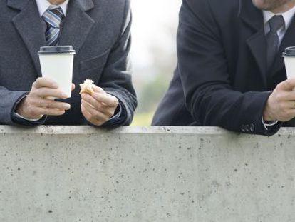Two workers enjoy a coffee break.