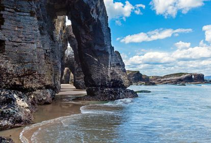 """On the coast of northern Spain near the Galician town of Ribadeo, waves crash against a series of arches that resemble a great cathedral. In fact, the proper name of this beach is Praia de Augas Santas (""""Holy Waters"""" in Galician). It's advisable to visit during low tide to admire the sand from the caves and the arches."""