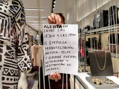 Andrea Pascual, who works at the Parfois store in Puerta del Sol, shows a sign she was given by a stranger ahead of the protests.