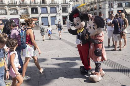 Minnie and Mickey Mouse with tourists who want to pay for a photograph with them.