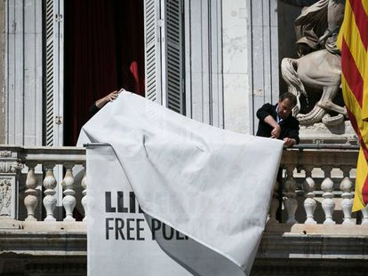 A banner in support of jailed separatist leaders is removed from Catalan government HQ.