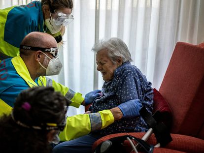 Health workers help an elderly patient in Madrid.