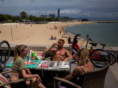 Local customers sit in a restaurant next to a beach in Barcelona.