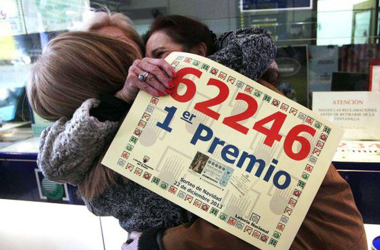 Three women celebrate their winning Christmas lottery ticket in Leganés, Madrid on Sunday.