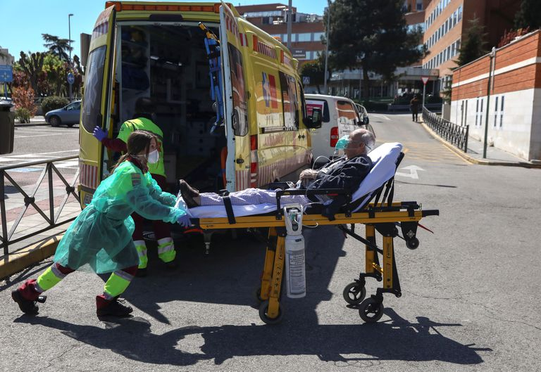 A healthcare worker wearing a protective face mask and suit transports a patient from an ambulance to the emergency unit at 12 de Octubre hospital during the coronavirus disease (COVID-19) outbreak in Madrid, Spain March 28, 2020. REUTERS/Sergio Perez