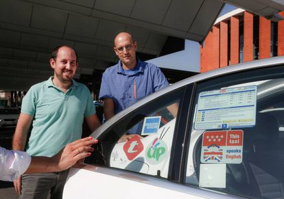Taxi drivers Daniel Elizo (left) and Oscar López next to a vehicle bearing a sticker reading 'This taxi speaks English.'