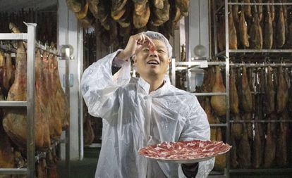 A distributor for the Spanish company Embutidos Fermín tries a piece of ham.