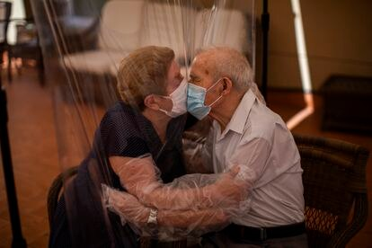 Agustina Cañamero, 81, and Pascual Pérez, 84, embrace via a plastic screen to avoid contracting the coronavirus in a home in Barcelona, on June 22, 2020.