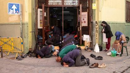The Muslim faithful pray at the doors of Baitul Mukarram mosque in Lavapiés, Madrid.