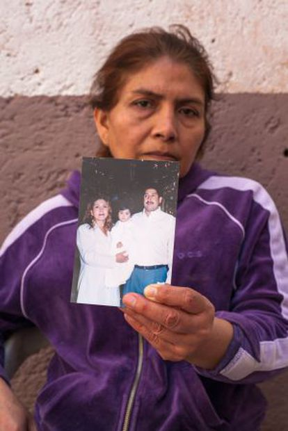 Yolanda Guerrero holds up a photograph taken of herself and her family before the operation.