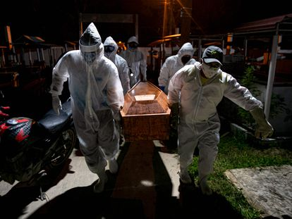 Gravediggers carry the coffin of a victim of the coronavirus for its burial in Breves in the Brazilian state of Para.