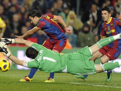 Iker Casillas dives to stop Xavi and David Villa during a Real Madrid-Barça encounter.