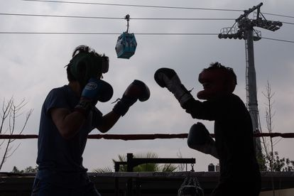 Two locals of Iztapalapa practice boxing near a cable car station.