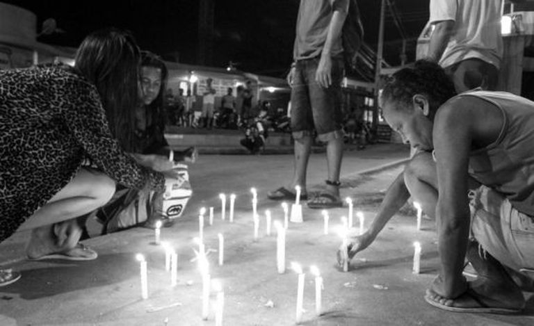 Residents of a building in Alemão, in Rio de Janeiro, light candles after the violent death of a child in April.