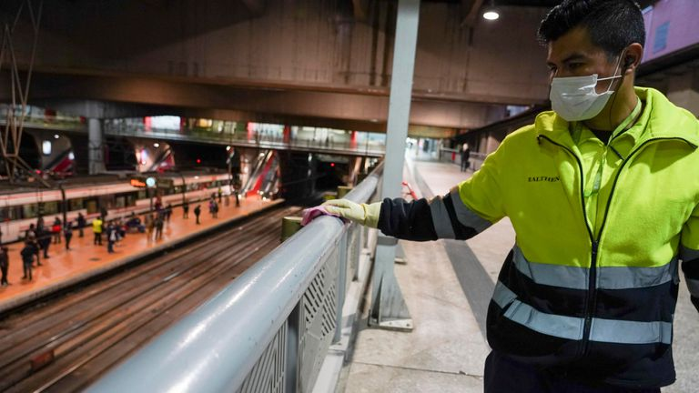 A worker cleans a railing at Atocha train station in Madrid.