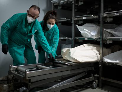 Funeral workers prepare to transfer a body to a coffin in Barcelona.