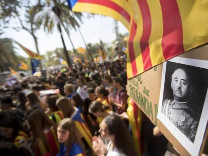 Hundreds of people congregate at a courthouse in Barcelona, and one person holds up a photo of Franco.