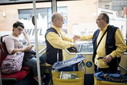 Juan Tamayo (left) talks with a colleague on the bus taking them to their delivery areas.