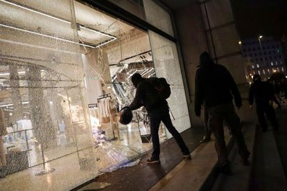 Protesters smash a shop window in Barcelona.