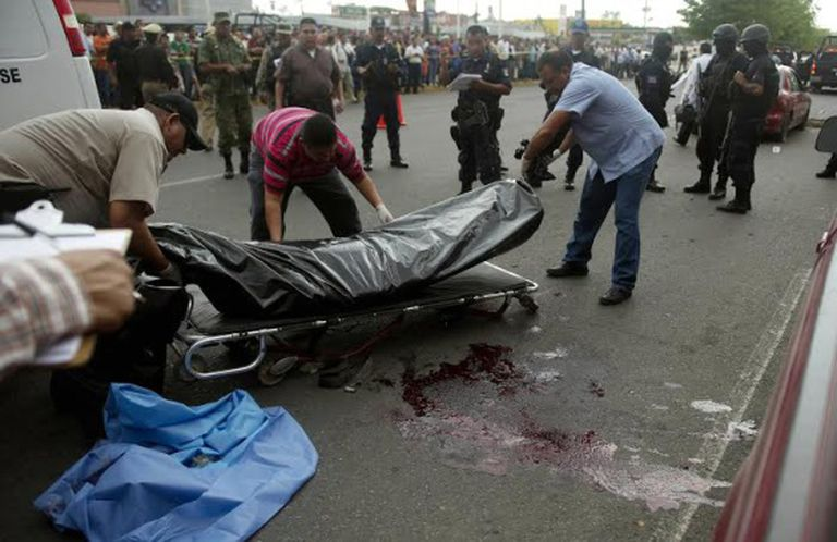 Forensics experts move the bodies of two police officers killed in Culiacán