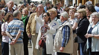 A tour guide leading a group of tourists in the Mediterranean city of Valencia.