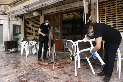 Workers in a cafe in Málaga prepare to open on Monday.