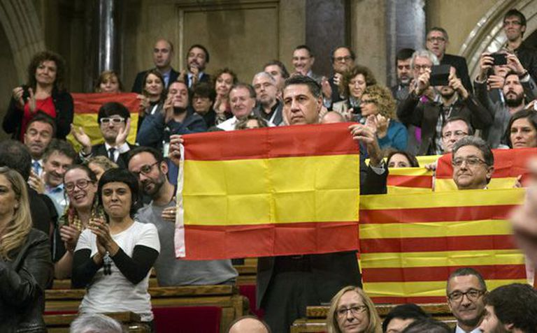 PP deputies hold up Spanish and Catalan flags after the vote.