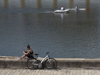 A woman sits by the Guadalquivir river in Seville, Andalusia, which will move to Phase 3 on Monday.