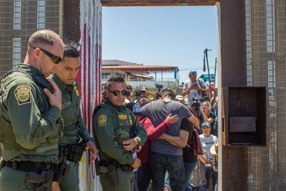 US border guards watch as families from both sides of the fence greet each other.