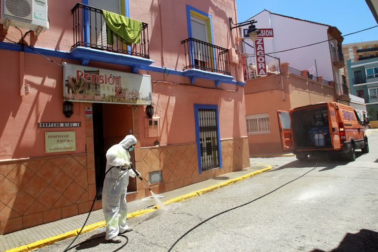 An Algeciras city worker disinfects the outside of a hostel following a coronavirus outbreak.