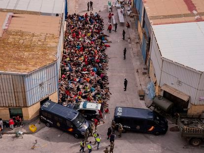 Unaccompanied foreign migrants at the door of a warehouse being used as a temporary shelter in Ceuta.