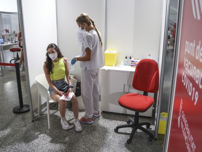 A health worker vaccinates a teenager in Valencia.