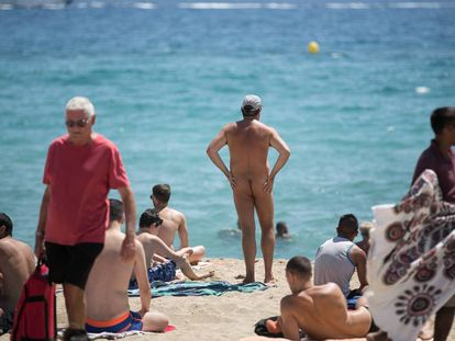 A nudist on Mar Bella beach surrounded by clothed bathers.