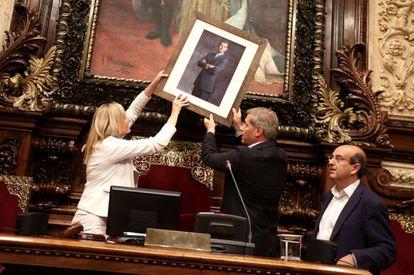 The PP leader in Barcelona, Alberto Fernández Díaz, places the portrait of Felipe VI inside city council.