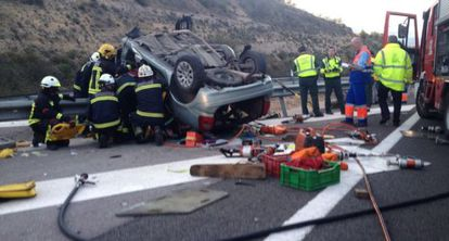 Firefighters extract bodies from a car following an accident in Granada.