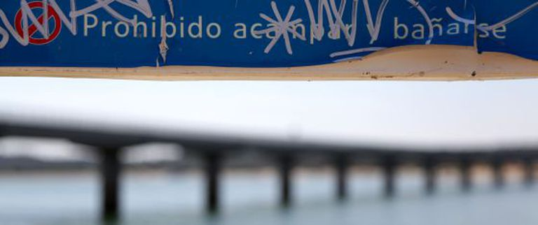A graffiti-daubed sign banning swimming and camping at the Valmayor reservoir where two young girls drowned Sunday