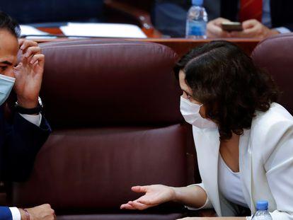 Madrid premier Isabel Díaz Ayuso (r) talks with her deputy Ignacio Aguado in the regional parliament.