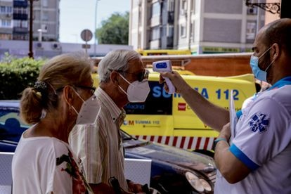 A healthcare worker takes a man's temperature in Villaverde, Madrid.